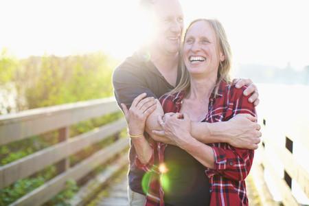 Portrait happy  affectionate couple hugging on sunny summer footbridge