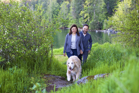 Happy couple with dog hiking along lush green lakeside