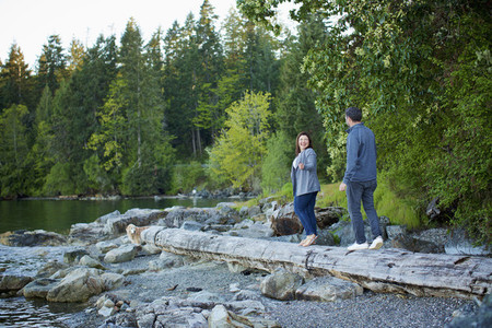 Happy couple walking on fallen log at lakeside in woods