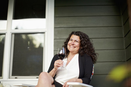 Happy woman drinking red wine on front porch