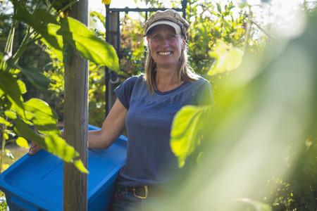 Portrait confident smiling farmer in sunny vegetable garden