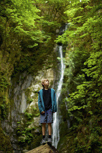 Curious boy in woods with waterfall