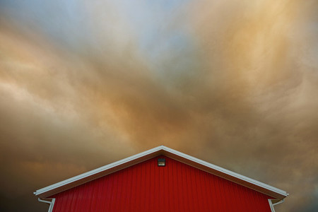 Orange clouds forming in dramatic sky over vibrant red barn