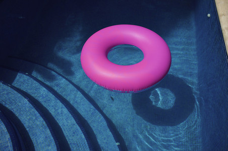 Bright pink inflatable ring in sunny blue swimming pool