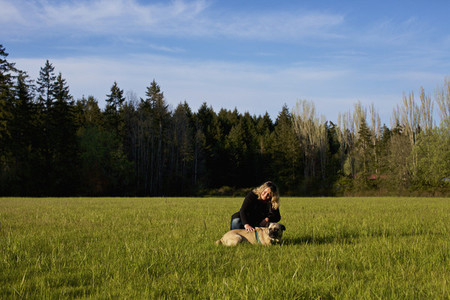 Woman with dog in sunny  rural field