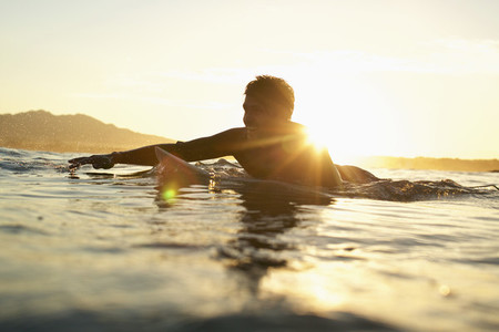 Happy male surfer paddling out on sunny sunset ocean