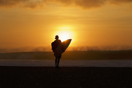 Silhouetted male surfer watching ocean wave from sunset beach