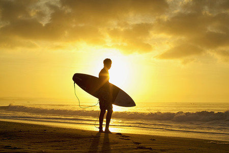 Silhouetted male surfer with surfboard on tranquil