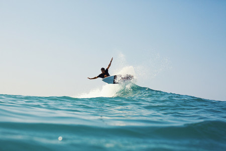 Male surfer riding turquoise blue ocean wave
