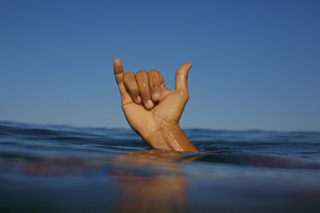 Close up male surfer gesturing shaka sign in ocean