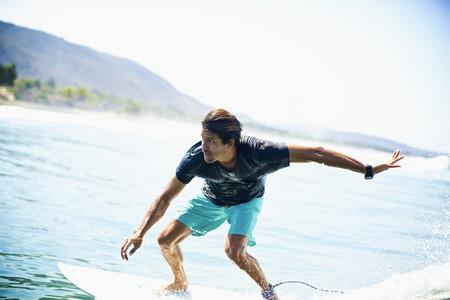 Focused male surfer riding ocean wave