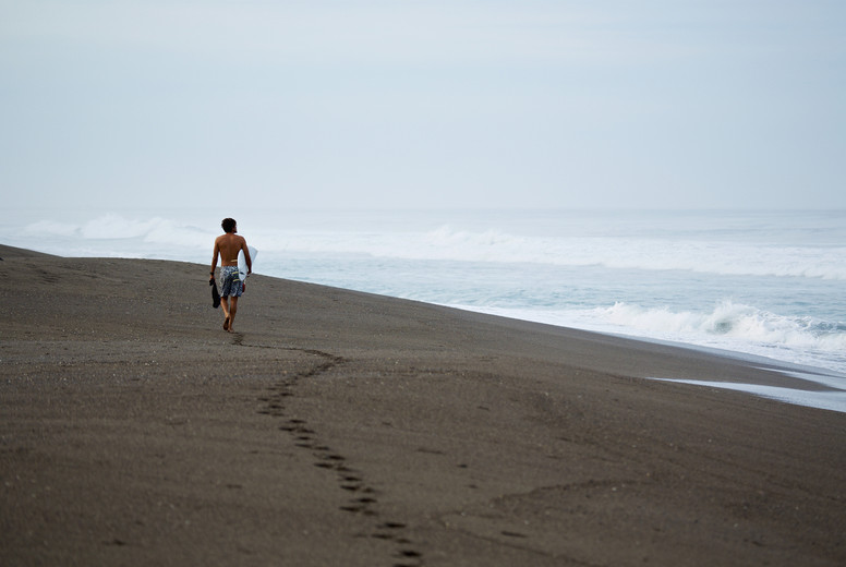 Male surfer walking with surfboard on wet sand beach