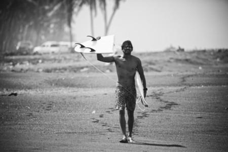 Portrait male surfer holding broken surfboard on beach