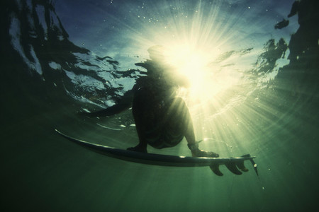 Underwater ocean view male surfer balancing on surfboard