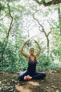 Serene  fit female personal trainer stretching in forest