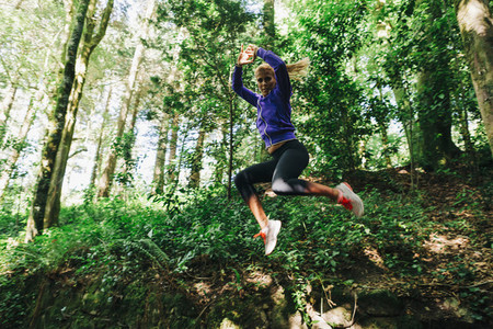 Portrait carefree female personal trainer hiking jumping in forest