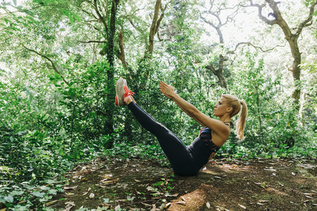 Fit female personal trainer exercising in forest