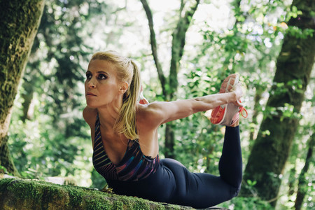 Focused fit female personal trainer stretching in forest