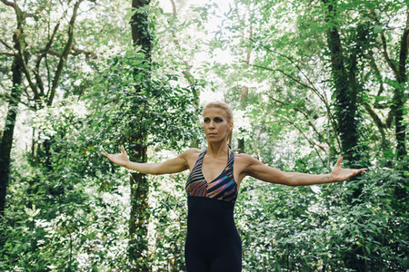 Fit female personal trainer exercising  stretching arms in forest
