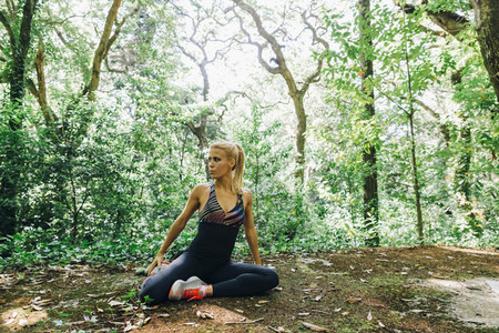 Fit female personal trainer exercising stretching in forest