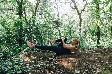Fit female personal trainer exercising  stretching legs in forest
