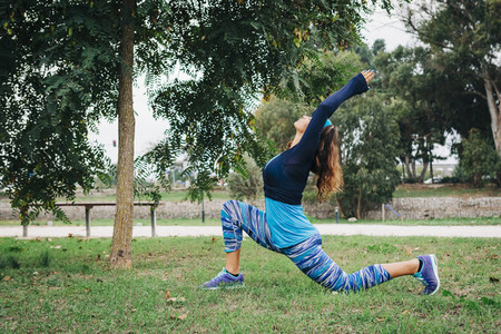 Fit female personal trainer exercising  stretching in park