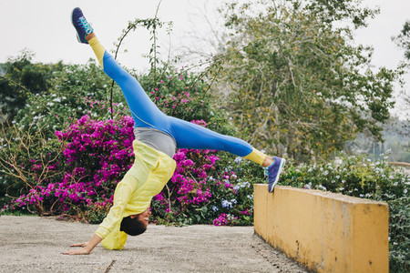 Fit female personal trainer exercising  stretching upside down in park