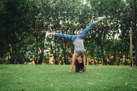 Portrait fit  carefree female personal trainer doing handstand in park