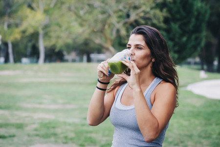 Fit female personal trainer drinking green smoothie in park