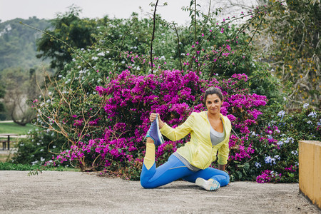 Portrait fit female personal trainer exercising stretching in park