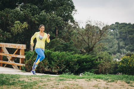 Portrait fit female personal trainer running in park