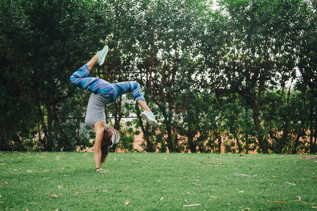 Fit carefree female personal trainer doing handstand in park