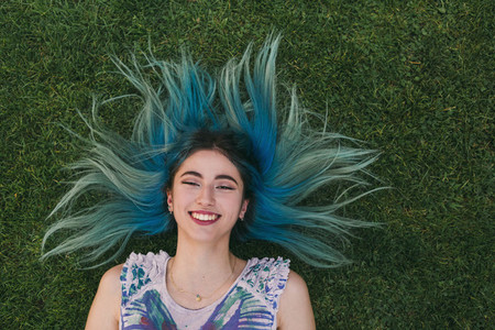 Overhead portrait carefree young woman with blue hair laying in grass
