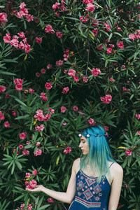 Serene young woman with blue hair standing below flowering tree