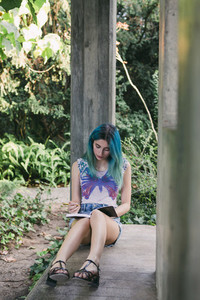 Young woman writing in journal in park