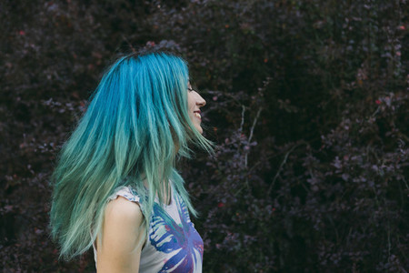 Profile carefree young woman with blue hair