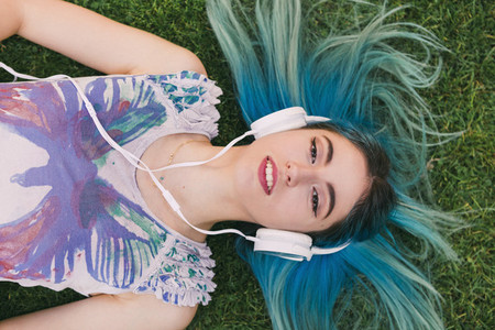 Overhead portrait young woman with blue hair listening to music