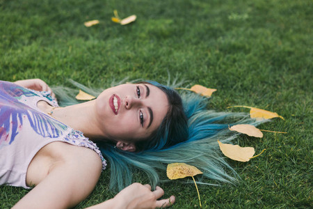 Portrait serene young woman with blue hair laying in grass with autumn leaves
