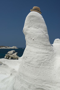 Hat perched on white rock formation Milos Greece