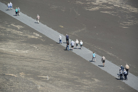 Tourists walking along volcano path  Portugal