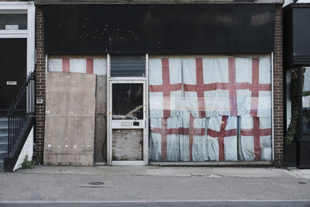 English flags covering abandoned storefront  Margate  England