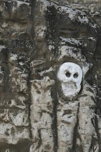 Skeleton face carved into rock