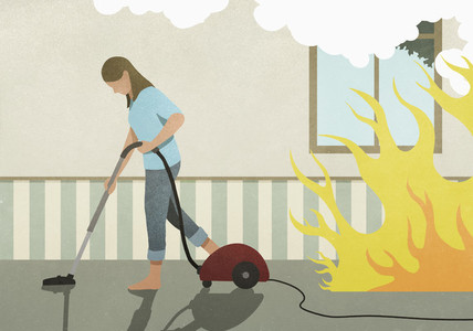 Flames and smoke behind oblivious woman vacuuming carpet