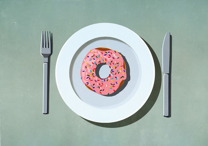Pink donut with sprinkles on plate