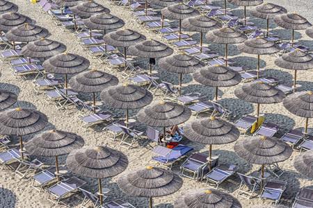 Straw beach umbrellas and lounge chairs on tourist resort beach