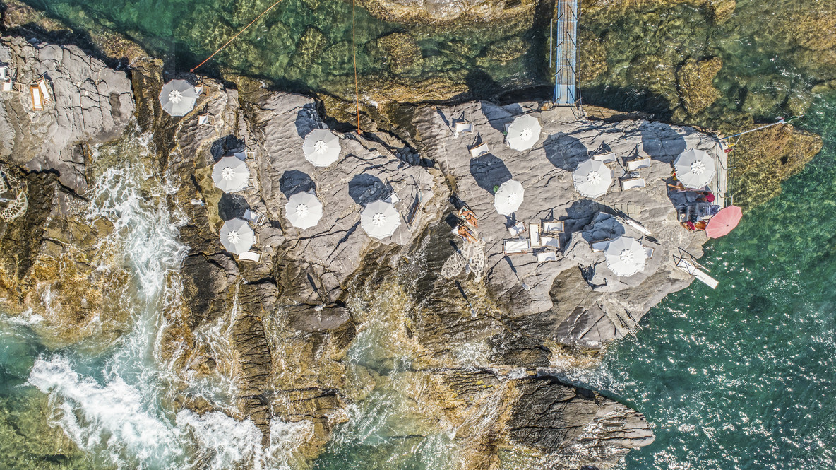 Aerial view from above beach umbrellas on sunny rocks above ocean