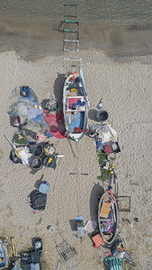 View from above fishing boats and equipment strewn on beach