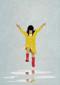 Carefree girl jumping in rain puddles
