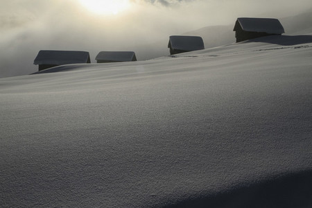 Snow covered cabins on sunny tranquil mountain slope Switzerland