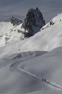 Snowshoers on sunny  snowy mountain slope  Switzerland